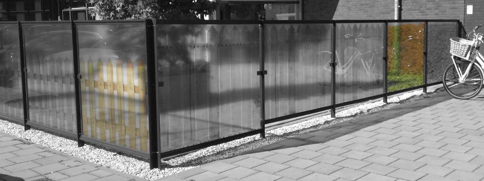 Metalen hek met glazen panelen met daarop foto's van houten hekjes en een heg.